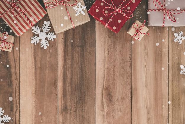 Sfondo di natale con scatole regalo e decorazione fiocco di neve su un tavolo di legno