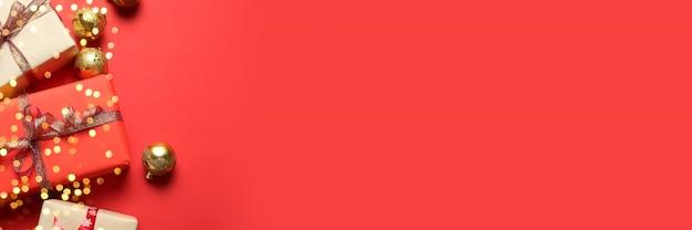 Sfondo di natale con scatole regalo, nastri rossi, decorazioni dorate su sfondo rosso. natale, inverno, concetto di nuovo anno. vista dall'alto, copia spazio