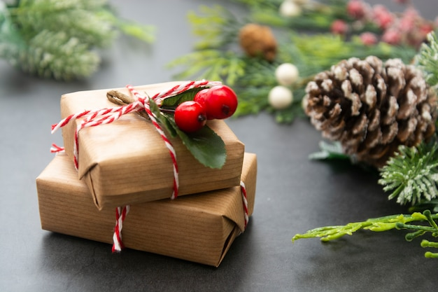 Sfondo di natale con scatole regalo, rami di abete e pigne.