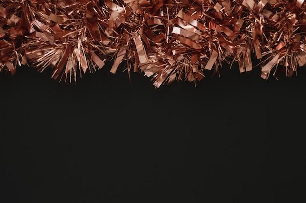 Sfondo di natale con spazio nero per il testo. decor con ghirlanda in oro rosa. sfondo per il nuovo anno 2020.