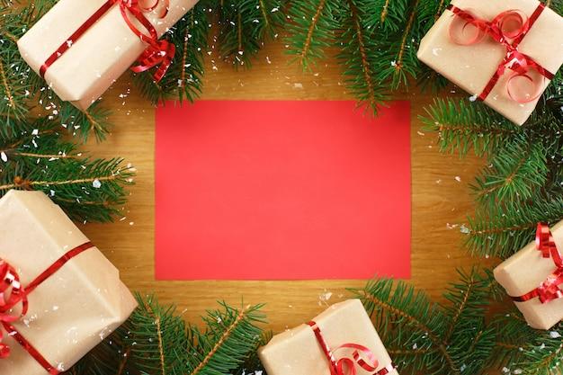 Sfondo di natale con taccuino bianco circondato da decorazioni natalizie.