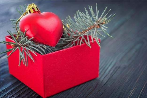 Sfondo di natale: confezione regalo rossa con un giocattolo di natale a forma di cuore e rami di abete