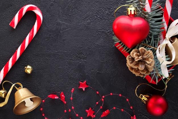 Sfondo di natale: confezione regalo rossa con un giocattolo di natale a forma di cuore, una campana d'oro, rami di abete, caramelle di natale, ghirlanda