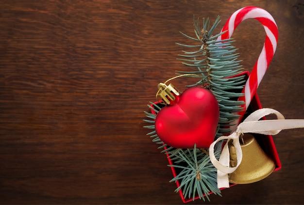 Sfondo di natale: confezione regalo rossa con un giocattolo di natale a forma di cuore, una campana d'oro, rami di abete e caramelle di natale