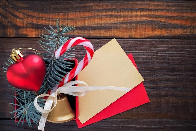 Sfondo di natale: confezione regalo rossa con un giocattolo di natale a forma di cuore, una campana d'oro, rami di abete e carta per testo di congratulazioni