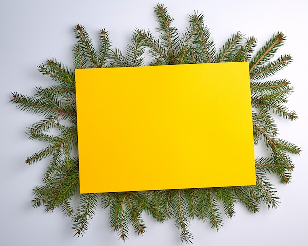 Sfondo di natale di congratulazioni con un foglio giallo vuoto e rami verdi