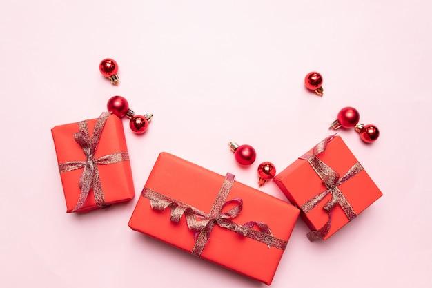 Sfondo di natale di piccoli regali rossi con nastro d'oro, palline rosse su sfondo rosa. concetto minimale.