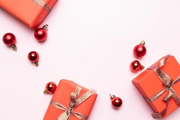 Sfondo di natale di piccoli regali rossi con nastro d'oro, palline su sfondo rosa. minimo concetto di capodanno.