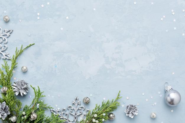 Sfondo di natale e capodanno con cornice di decorazioni d'argento su spazio blu copia.