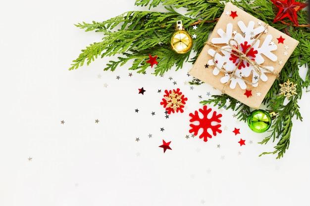 Sfondo di natale e capodanno con ramo di thuja, decorazioni e presente avvolti in carta artigianale con fiocchi di neve.
