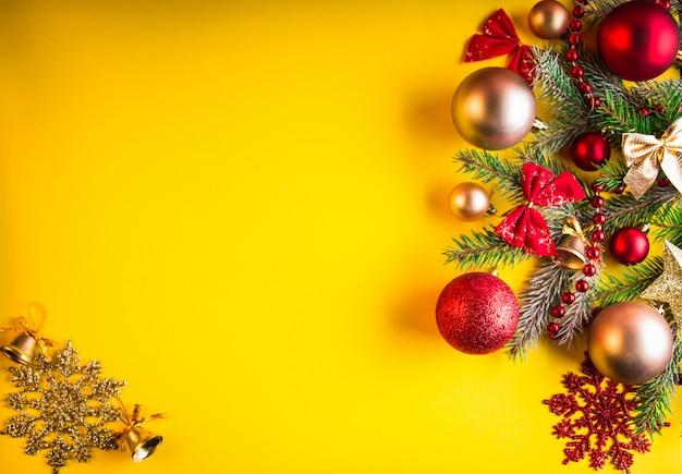 Sfondo di natale giallo decorato con abete e giocattoli