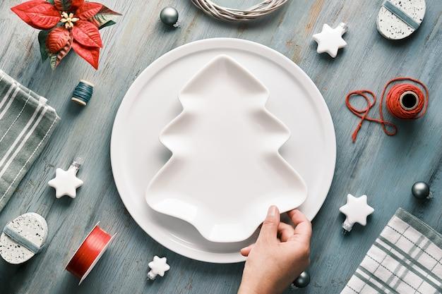 Sfondo di natale in grigio, rosso e bianco con la mano che tiene il piatto sul tavolo. piatto geometrico laici con decorazioni natalizie.
