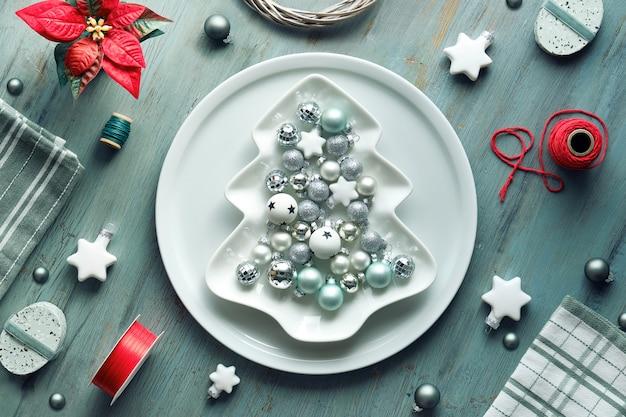 Sfondo di natale in zolla grigia, rossa e bianca sul tavolo. piatto geometrico laici con decorazioni natalizie. forma di albero di natale ...