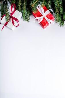 Sfondo di natale per biglietto di auguri, con rami di abete e scatole regalo con nastri, su sfondo bianco vista dall'alto copia spazio per il testo