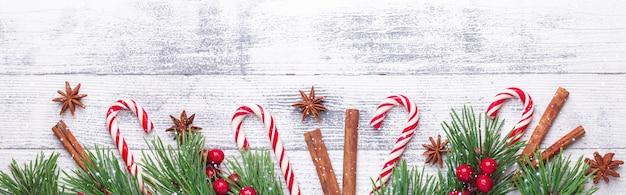 Sfondo di natale. rami di abete, bastoncino di zucchero e regali su fondo in legno banner orizzontale effetti neve