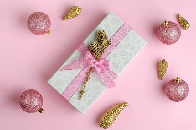Sfondo di natale rosa. confezione regalo con nastro e palline distesi.