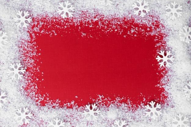 Sfondo di natale rosso con cornice di neve e fiocchi di neve.