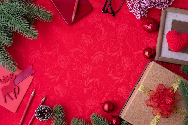 Sfondo di natale rosso con decorazioni natalizie, vista dall'alto.