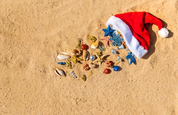 Sfondo di natale sulla spiaggia con conchiglie sulla sabbia.