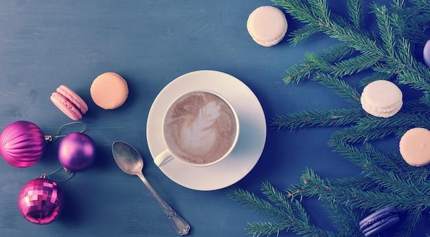 Sfondo di natale - tazza di cappuccino con torta, macarons, giocattoli di natale e rami di alberi