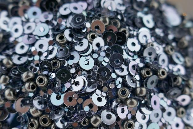Sfondo di paillettes festivo. trama di close-up di paillettes e perle di metallo. motivo decorativo di perline e paillettes