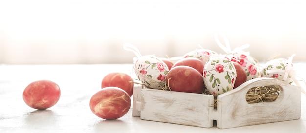 Sfondo di pasqua con un cesto e uova rosse con fiori
