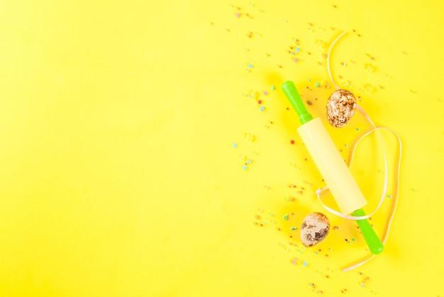 Sfondo di pasqua con uova di quaglia mattarello e zucchero spruzzando su sfondo giallo concetto di vacanze di primavera