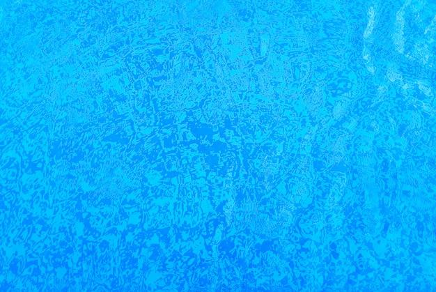 Sfondo di piastrelle di una piscina, bianco e blu, attraverso l'acqua.