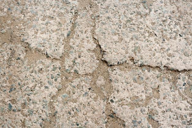 Sfondo di pietra. parte della pavimentazione in cemento con piccoli ciottoli e sabbia, martellata in fessure.