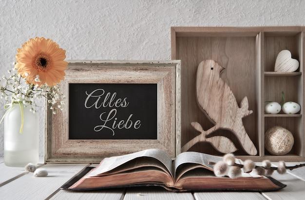 Sfondo di primavera con un libro aperto e decorazioni stagionali, testo alles liebe in tedesco
