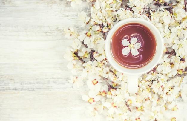Sfondo di primavera, fiori e tè. messa a fuoco selettiva