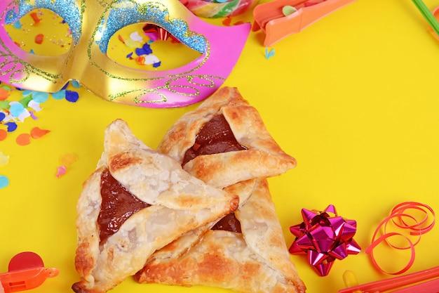 Sfondo di purim con maschera di carnevale, costume da festa e biscotti hamantaschen.
