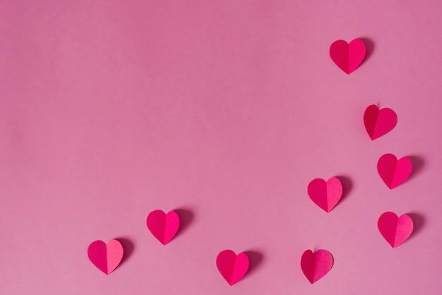 Sfondo di san valentino. bordo o cornice di cuori di carta rosa.