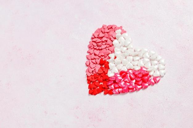 Sfondo di san valentino, caramelle a forma di cuore, spruzza, vista dall'alto