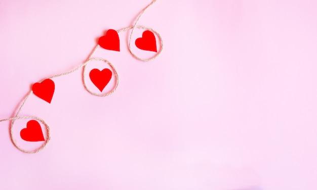 Sfondo di san valentino con cuori rossi e accessori su sfondo rosa. sfondo di forme d'amore.