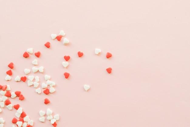 Sfondo di san valentino con cuoricini rossi e bianchi su sfondo rosa.