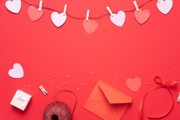 Sfondo di san valentino con decorazioni a forma di cuore, regalo e nastri. vista dall'alto