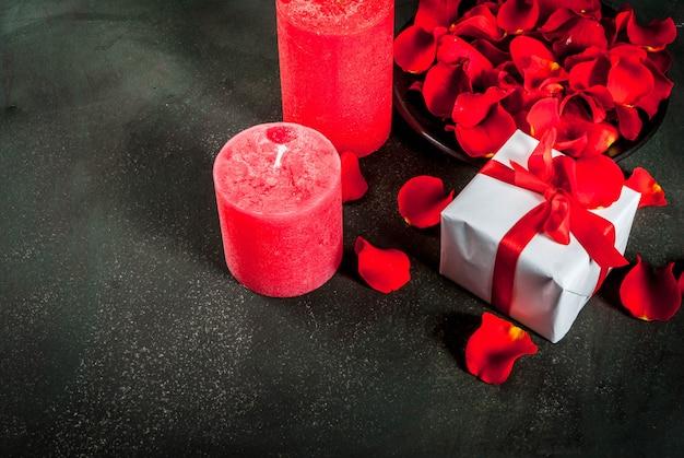 Sfondo di san valentino con petali di fiori rosa, bianco avvolto in confezione regalo con nastro rosso e vacanza candela rossa, su sfondo di pietra scura, copia spazio