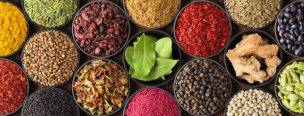 Sfondo di spezie colorate, vista dall'alto. collezione condimento indiano in coppe