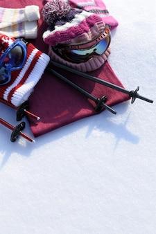 Sfondo di sport invernali con bastoncini da sci, occhiali, cappelli e guanti