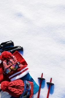 Sfondo di sport invernali neve con bastoncini da sci, occhiali, cappelli e guanti con copyspace.