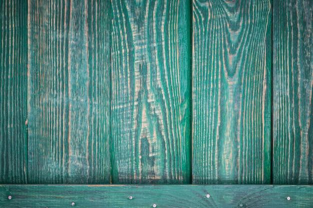 Sfondo di tavole di legno con una barra orizzontale con tracce di vernice verde. orizzontale.