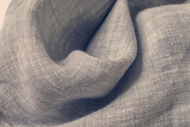 Sfondo di tessuto di lana sottile grigio-beige rannicchiato da un'onda morbida. il concetto di hygge, sensazioni di calore, tenerezza, cura, intimità.
