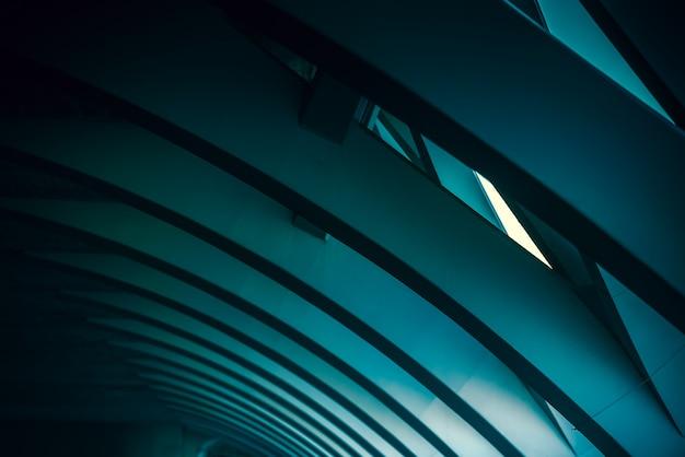 Sfondo di toni bluastri e atmosfera fredda e scura con colonne e linee di geometria ondulata.