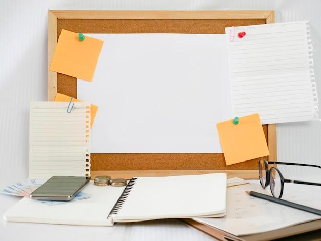 Sfondo di una tavola di legno, carta da lettere, carta bianca con attrezzatura intorno, come matite, occhiali, soldi, telefoni cellulari e calendari,