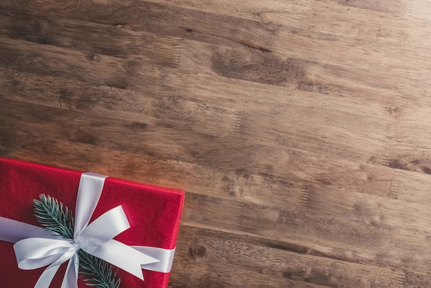Sfondo di vacanze di natale e capodanno con confezione regalo rosso sul tavolo di legno al confine