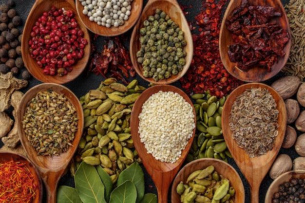 Sfondo di varietà di diverse spezie vivaci in cucchiai di legno