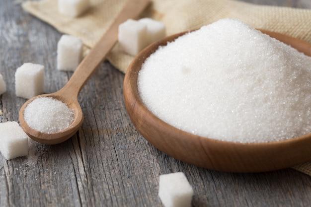 Sfondo di zucchero zollette di zucchero, zucchero semolato in cucchiaio e zolla. zucchero bianco su sfondo grigio ferro zincato. copia spazio.