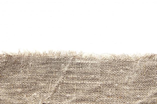 Sfondo e consistenza del tessuto di lino grezzo grigio con tessitura stretta e frangia lungo il bordo