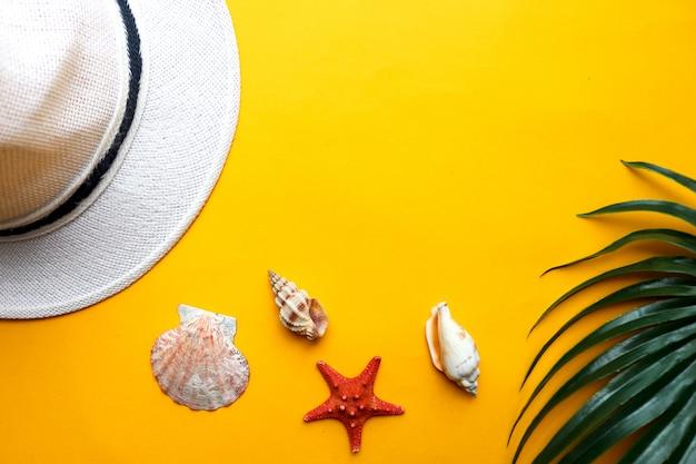 Sfondo estate con conchiglie, cappello spiaggia e foglia di palma su sfondo giallo. estate, vacanze al mare e concetto di viaggio